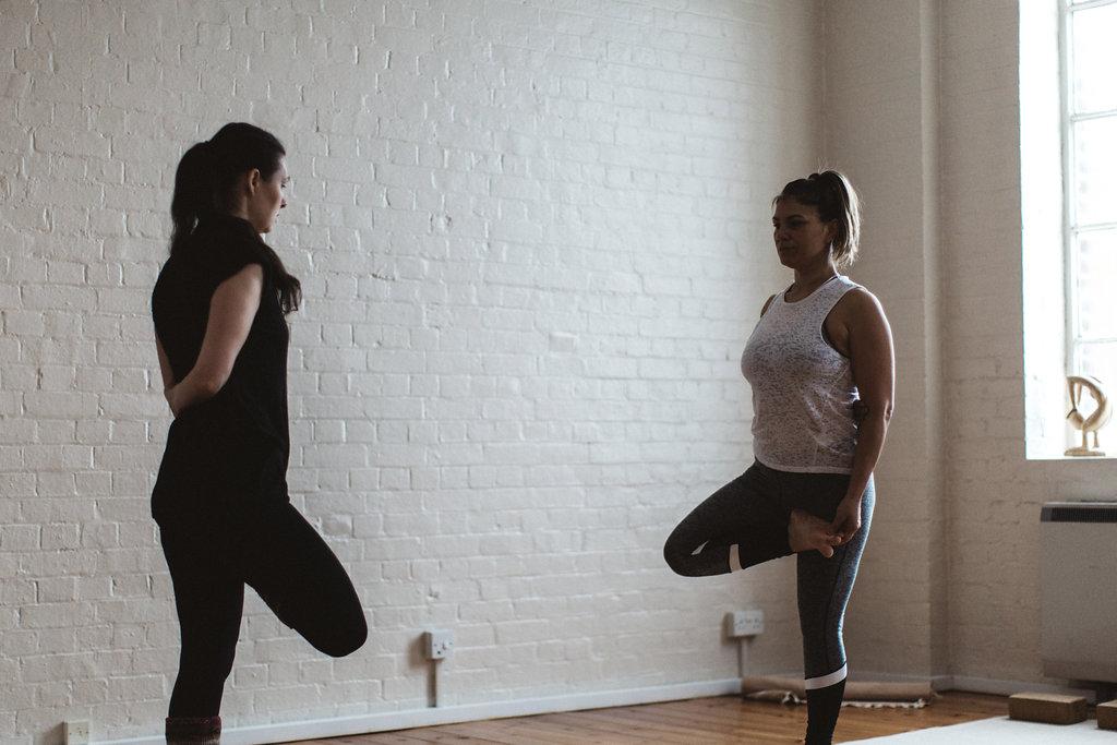 Sam and a student practicing Ardha Baddha Padmottanasana at the Yoga Akasha studio in East Grinstead.