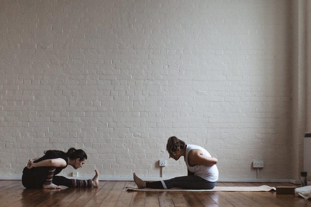 Teacher and student practicing ashtanga yoga.
